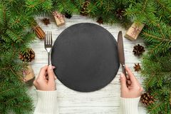 Top view girl holds fork and knife in hand and is ready to eat. Empty black slate plate on wooden christmas background. holiday di stock photos