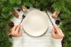 Top view girl holds fork and knife in hand and is ready to eat. Empty plate round ceramic on wooden christmas background. holiday royalty free stock photos