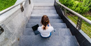 top view of the Girl with laptop and smartphone sits on a ladder. She is in jeans and a white t-shirt, steps from gray granite stock photo