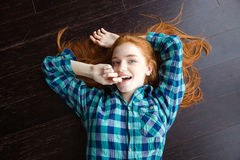 Top view of  girl in plaid shirt lying on floor Royalty Free Stock Photo