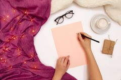 Top view of girl`s hand writing in notepad placed on white surface with coffee cup and other items. Mock up Royalty Free Stock Photography
