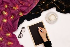 Top view of girl`s hand writing on small black wooden board on white surface with coffee cup and other items. Mock up Stock Image