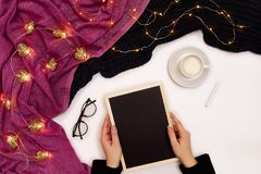 Top view of girl`s hand writing on small black wooden board on white surface with coffee cup and other items. Mock up Stock Photo