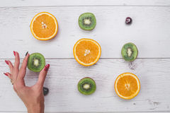 Top view of girl`s hands, placed on white desktop with fruits. Royalty Free Stock Photography