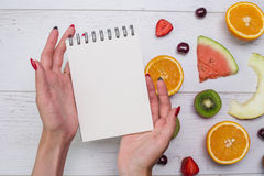 Top view of girl`s hands, placed on white desktop with fruits. Stock Photo