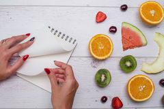 Top view of girl`s hands, placed on white desktop with fruits. Stock Photography