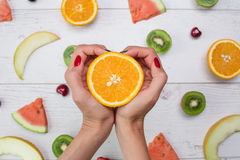 Top view of girl`s hands, placed on white desktop with fruits. Royalty Free Stock Photo