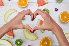 Top view of girl`s hands, placed on white desktop with fruits. Stock Image