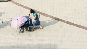 Top view of girl use wheel baby chair walk in pedestrian street. The top view of girl use wheel baby chair walk in pedestrian street stock photos