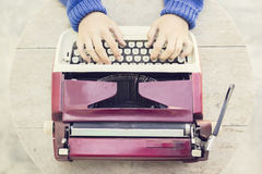 Top view on the girl with vintage typewriter on wooden table Royalty Free Stock Image