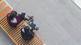 Top view of girls group use smart phone and talk on wood bench. The top view of girls group use smart phone and talk on wood bench royalty free stock photos