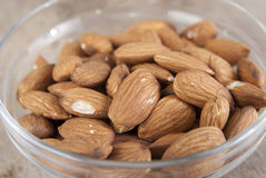 Top view of glass bowl full of almonds. Close up photo Royalty Free Stock Photography