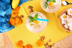 Top view of a glass full of a cocktail, dried apricots, mint, a spoon, a plate of lokum on a colorful background. stock photography