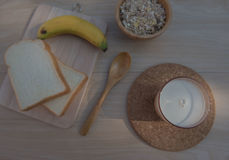 Top view Glass of milk with bread and banana for breakfast  on wooden table. morning sunshine. Stock Images