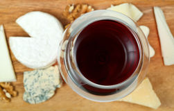 Top view of glass of red wine and various cheeses Stock Images