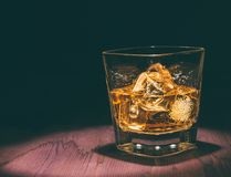 Top of view of glass of whiskey with ice cubes on wood table, warm atmosphere, time of relax with whisky. With space for text Royalty Free Stock Photos