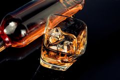 Top of view of glass of whiskey near bottle on black table with reflection Stock Photo