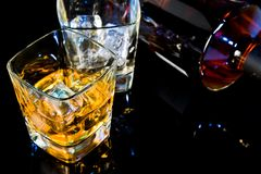 Top of view of glass of whiskey near bottle on black table with reflection Stock Image