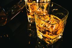 Top of view of glass of whiskey near bottle on black table with reflection Royalty Free Stock Photo