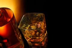 Top of view of glass of whiskey near bottle on black table with reflection Royalty Free Stock Photos
