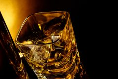 Top of view of glass of whiskey near bottle on black table with reflection, warm light Royalty Free Stock Photo