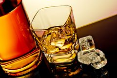 Top of view of glass of whiskey near bottle and ice cubes on table with reflection Stock Images