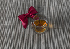 Top view for a glass of whiskey single malt, red bow Stock Images