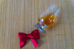 Top view for a glass of whiskey single malt, red bow. Bamboo background stock image