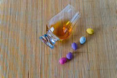 Top view for a glass of whiskey single malt, sweet colorful eggs. Bamboo background Royalty Free Stock Photography