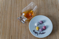 Top view for a glass of whiskey single malt, sweet colorful eggs. Happy easter, bamboo  background Royalty Free Stock Photo