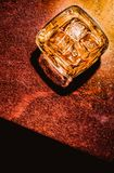 Top of view of glass of whiskey on wood table artistic style, warm atmosphere Royalty Free Stock Photo