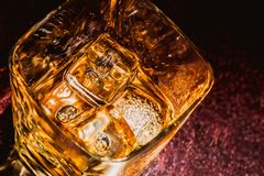 Top of view of glass of whiskey on wood table with focus on ices, warm atmosphere Stock Photography