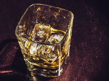 Top of view of glass of whiskey on wood table, warm atmosphere Royalty Free Stock Photos