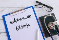 Top view of glasses,book,stethoscope,pen,clipboard and paper written with Autoimmune Disease. Healthcare and medical concept. Top view of glasses,book royalty free stock images