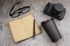 Glasses,camera, coffee to go, notebook with place for text and pen on a gray wood. Top view glasses,camera, coffee to go, notebook with place for text and pen on stock photo