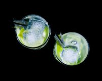 Top of view of glasses with cocktail and ice with lime slice on black background Stock Photography