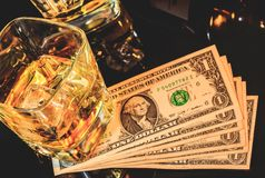 Top of view of glasses of whiskey near bottle on dollars money on a black table. Western theme style Stock Photos
