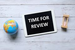 Top view of globe,sand clock and tablet written with Time For Review on wooden background. Top view of globe,sand clock and tablet written with Time For Review royalty free stock photos