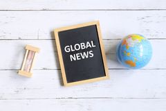 Global news. Top view of globe of world map,hourglass and blackboard written with & x27;GLOBAL NEWS& x27; on white wooden background Stock Images