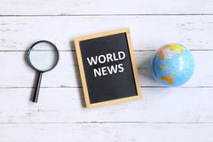 World news. Top view of globe of world map,magnifying glass, and blackboard written with & x27; WORLD NEWS& x27; on white wooden background Stock Images