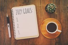 Top view 2019 goals list with notebook, cup of coffee over wooden desk. stock image