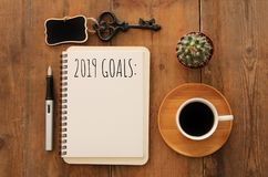 Top view 2019 goals list with notebook, cup of coffee over wooden desk. stock images