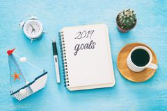 Top view 2019 goals list with notebook, cup of coffee over wooden desk. royalty free stock images