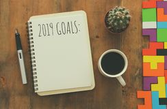 Top view 2019 goals list with notebook, cup of coffee over wooden desk. stock photo