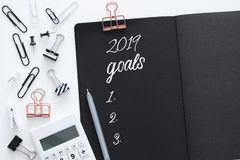 Top view 2019 goals list with notebook over white wooden desk. royalty free stock photos