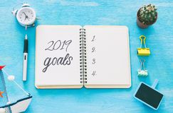 Top view 2019 goals list with notebook over wooden desk. royalty free stock photography
