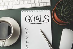 Top view of GOALS list on notepad on dark table, business success inspiration and motivation concept royalty free stock photos