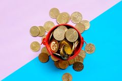 Top view of coin on a red pile. Top view of gold coins on red pile on blue and purple background. Two tone background. Business and finance theme Royalty Free Stock Photos