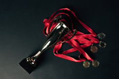 Top view of gold medals with red ribbons and champion goblet. On black floor Royalty Free Stock Images