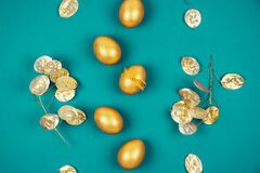 Top view of golden colored Easter eggs with dry flowers over bright green turquoise background.